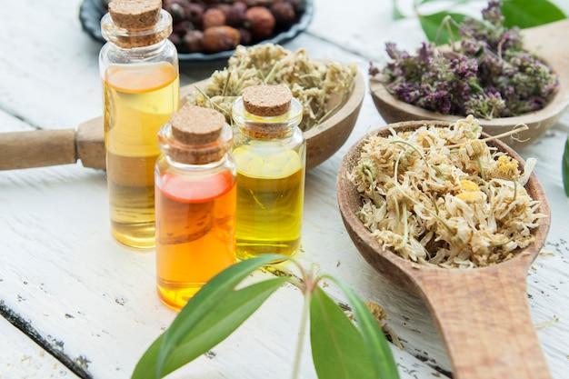 Сухие травы в деревянной ложке с эссенцией в стеклянных бутылках