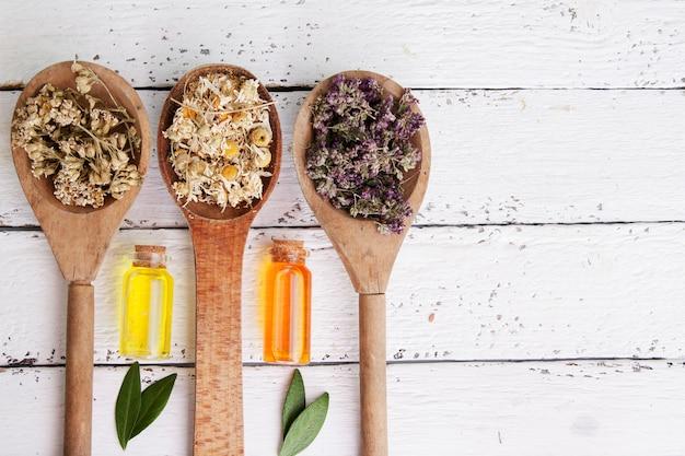 Сухие травы в деревянных ложках и эссенции в стеклянных бутылках
