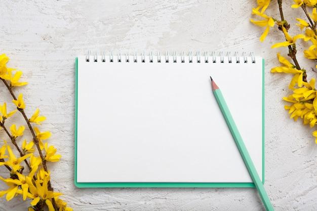 メモ用のメモ帳の空白のシート。春の枝と鉛筆。