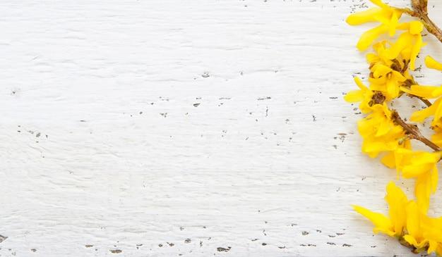 黄色い花を持つ木製の白いテクスチャです。
