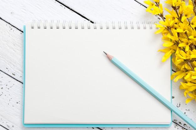 木製のテーブルのノートのメモ帳の空白のシート。春の枝と鉛筆。テキストのレイアウト。