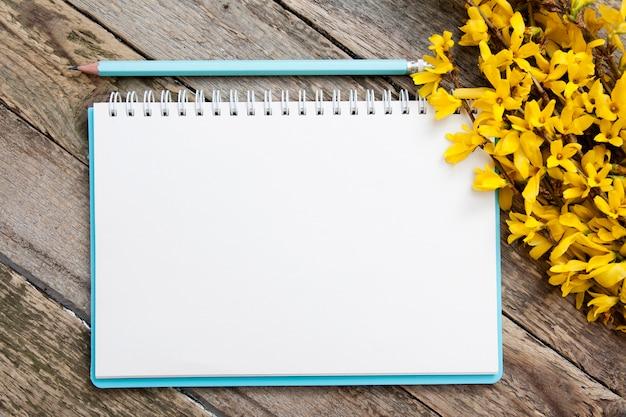 春の黄色い花の枝が付いているノートのメモ帳の空白のシート。テキストのモックアップ