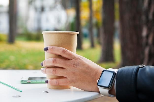 一杯のコーヒーの上の時計を持つ少女の手。秋の公園のテーブル。黄色の葉の背景に秋の気分