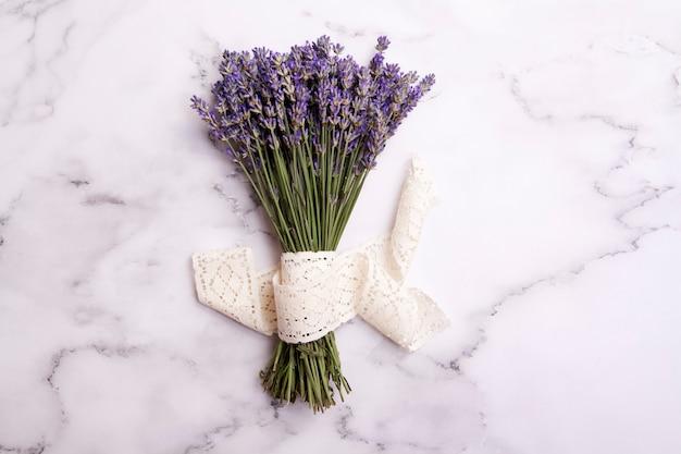Плоские лежали цветы лаванды в букет с кружевом на мраморном столе