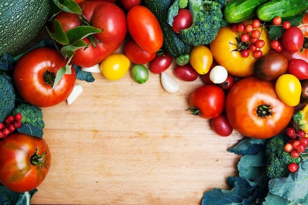 の木製の背景に新鮮な野菜のトップビュー。