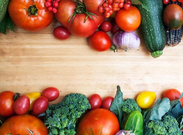 テキスト用の空き容量を持つ木材の背景に新鮮な野菜のトップビュー