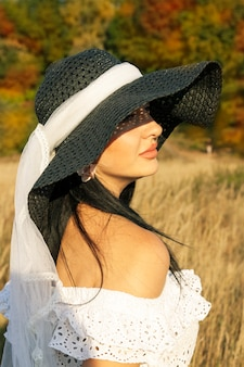 屋外の黒い帽子の美しいブルネットの女性。紅葉