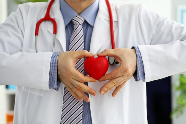 Мужской доктор медицины руки, держа и охватывающих красное игрушка сердце