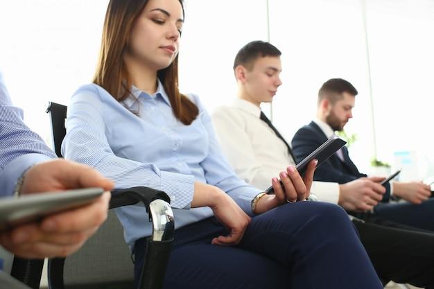 Группа деловых людей держит мобильное устройство