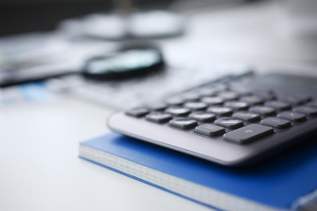 シルバー電卓とクリップボードの財務統計