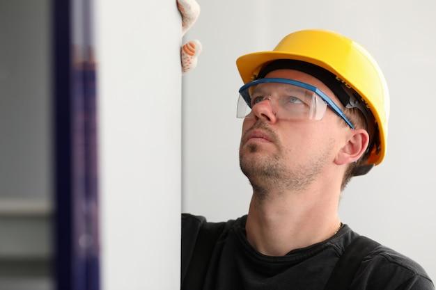Рабочий измеряет размер стены