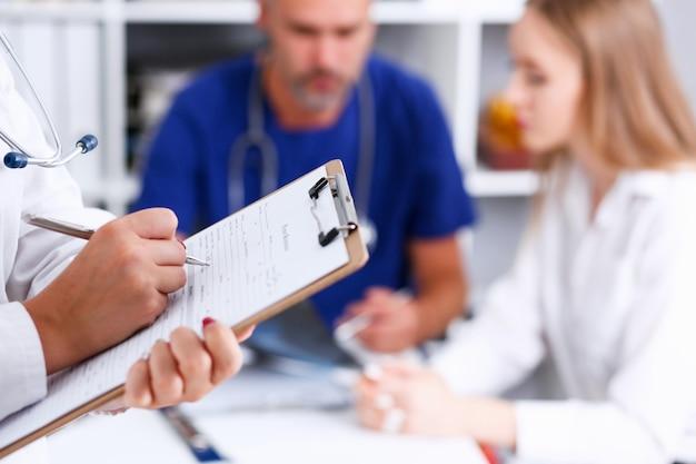 女性医師がクリップボードパッドを押し、病歴を記入