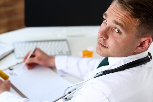 男性医学医師の手が薬の瓶を保持します。