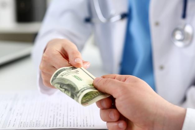 Женщина-врач держит банкноты за сто долларов