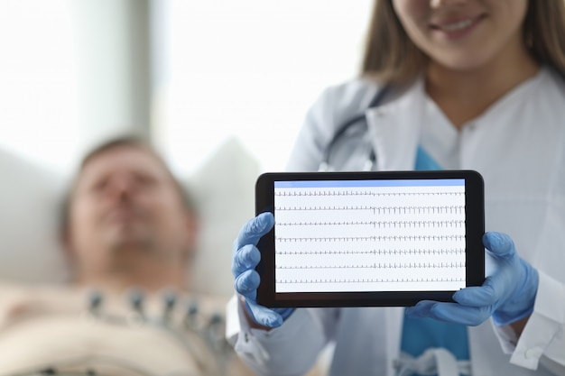Врач в клинике показывает пациентам кардиограмму планшета