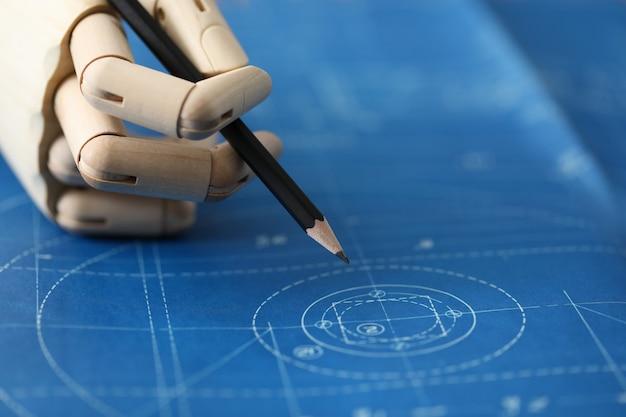 木製の手が青写真に対して黒鉛筆を保持します。