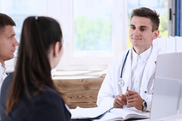 男性のかかりつけの医師がオフィスで若いカップルを注意深く聞く