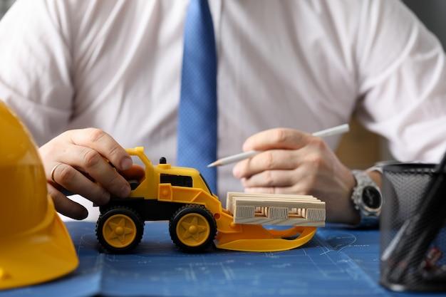 Мужской конструктор рука держать желтый трактор против