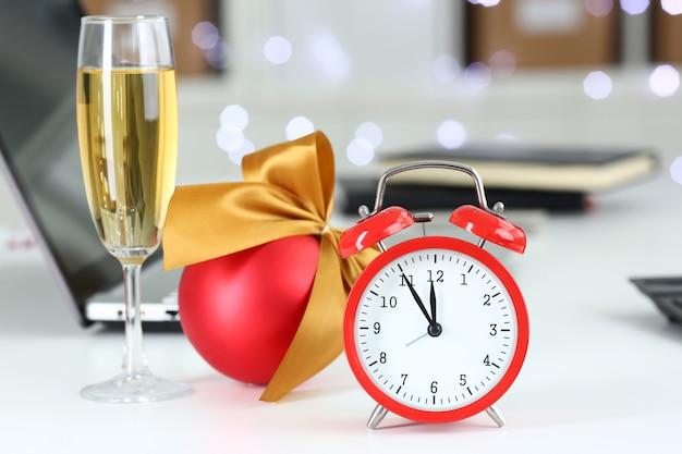 Красный будильник и бокал шампанского на офисном столе