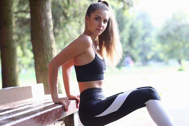 Стройная спортивная девушка делает отжимания на скамейке