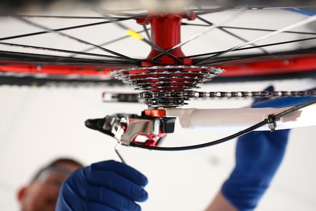 Человек в перчатке ремонтирует велосипедное колесо с ключом от дома