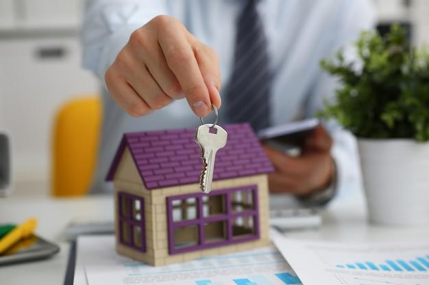 Мужская рука держит ключ от замка в руке