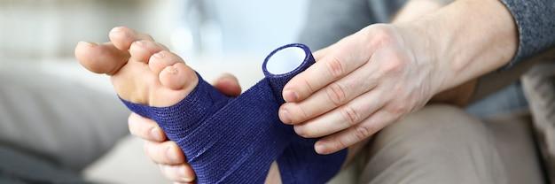 Человек, оборачивающий ноги эластичной повязкой