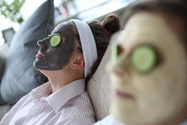人々は化粧品のマスクの顔でソファに横たわっています