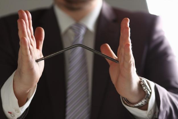 Мужчина в костюме и галстуке гнуть ногти с оружием крупным планом