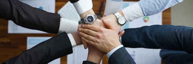 Группа мужчин в костюмах протягивает руки в единстве