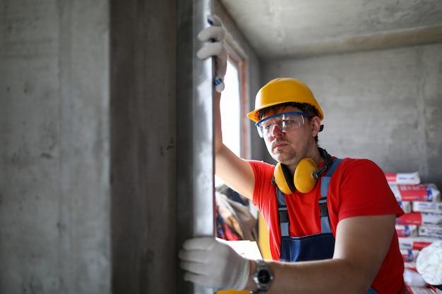 ヘルメットのビルダーは、窓のレベルの壁を測定します。