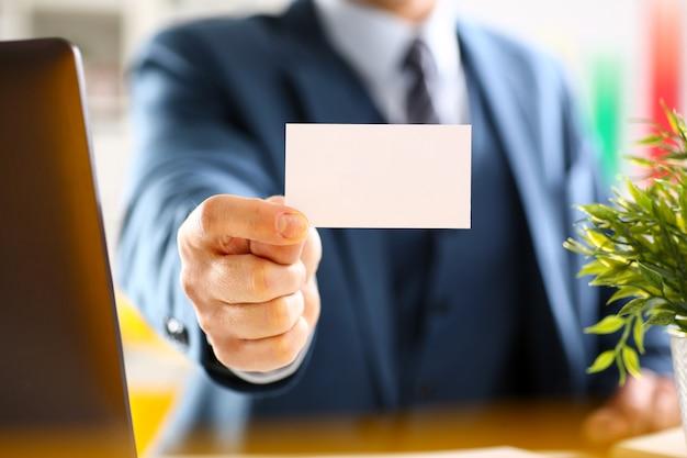 スーツの男性の腕は空白のコーリングカードを与える