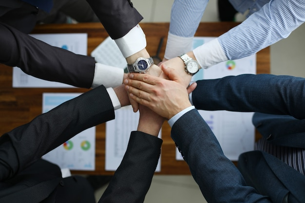 Группа мужчин в костюмах протягивает руки