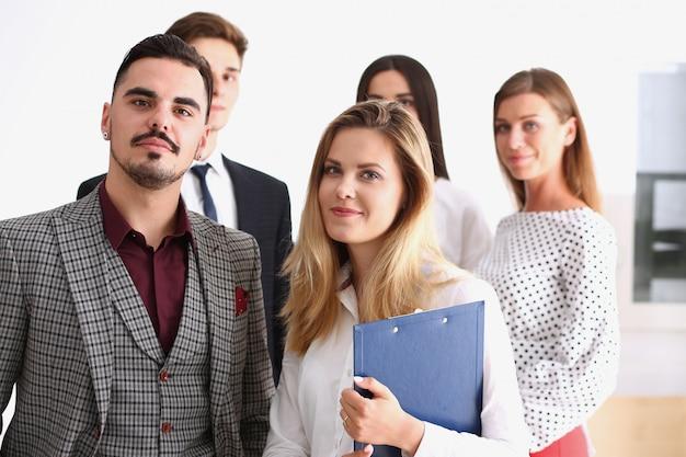 Группа улыбающихся людей стоят в офисе