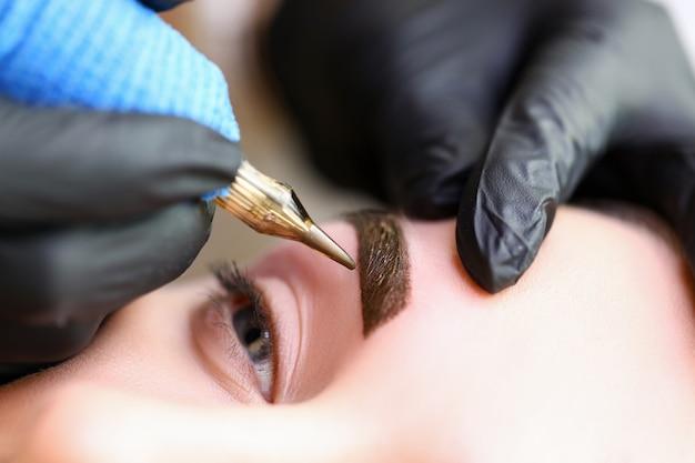 Косметологи руками делают перманентный макияж бровей