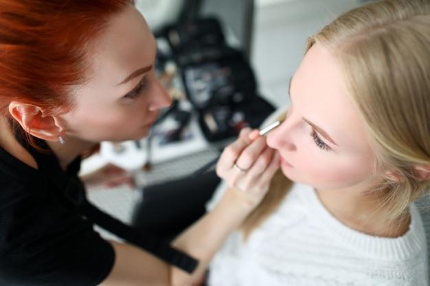 Визажист делает макияж лицом к блондинке