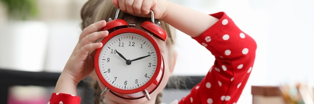 ベビードレスは大きな目覚まし時計で顔を覆った