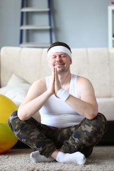 うれしそうな若い男が自宅でヨガの練習