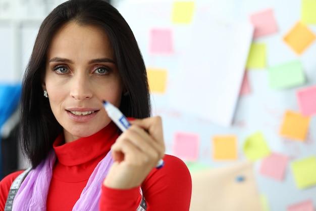 Стремящаяся молодая женщина держит маркер в руке