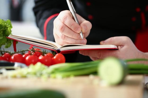 ノートに健康的な食事メニューを書くシェフの手