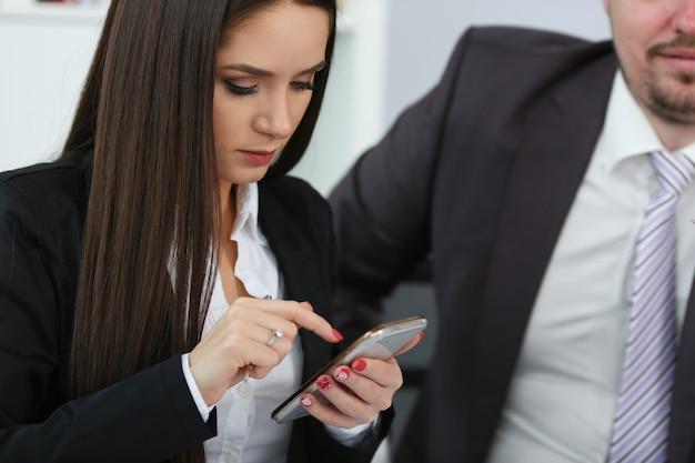 Красивая коммерсантка используя мобильный телефон на работе