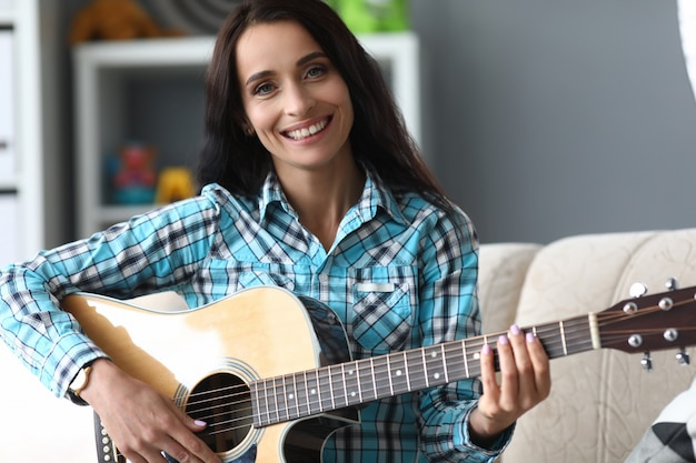 自宅でギターを弾く陽気な若い女性