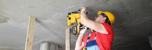 Строитель работает со специальным оборудованием на потолке. строитель шлем держит тяжелый инструмент. строитель работает перфоратором. монтажные пистолеты для бетона используются профессиональными строителями. вбивание гвоздей в твердые поверхности