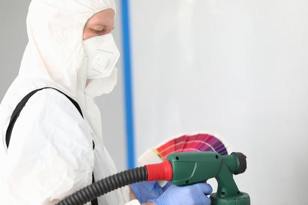 制服を着たビルダーが壁を塗る色を選ぶ