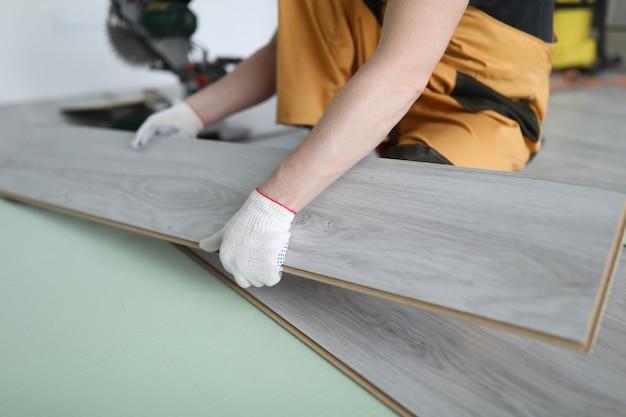 修理工がラミネートパネルの床のアパートを交換