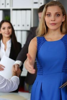 Женщина в голубом платье приветствует своего партнера