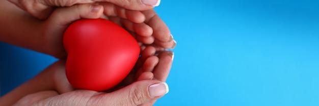 Крупным планом в женских ладонях детские руки и сердце