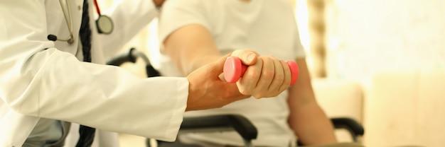 Человек с ограниченными возможностями сидит, разрабатывая руку гантели