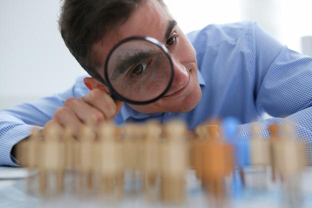 青いシャツのビジネスマンは拡大鏡を保持しています。
