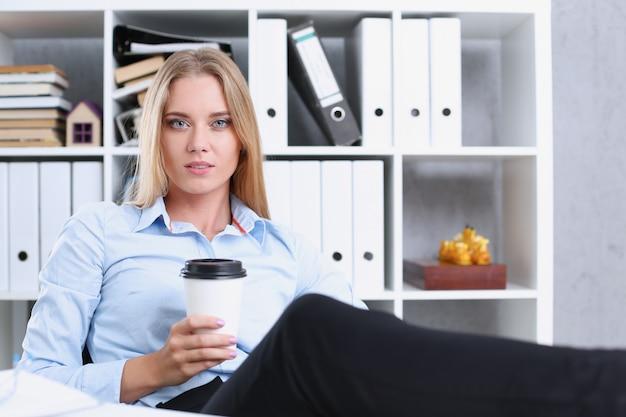 Улыбающаяся деловая женщина пьет кофе